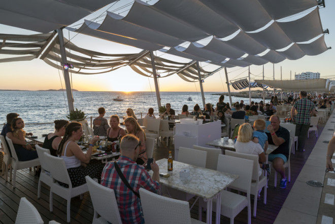 SAN ANTONI DE PORTMANY, IBIZA - MAY 15, 2015: People meet in bars coast to see the famous sunset and fun