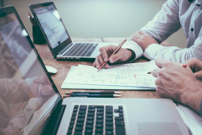 budget irlanda 2021 homens rabiscam contas em papel com computadores
